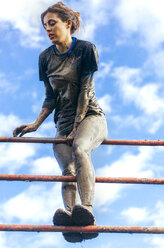Participants in extreme obstacle race climbing over hurdle - MGOF001404