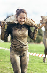 Participant in extreme obstacle race carrying sandbags - MGOF001407