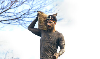 Participant in extreme obstacle race carrying sandbags - MGOF001410