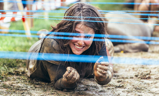Participants in extreme obstacle race crawling under electric wire - MGOF001413
