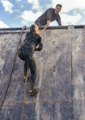 Participants in extreme obstacle race climbing wall - MGOF001416