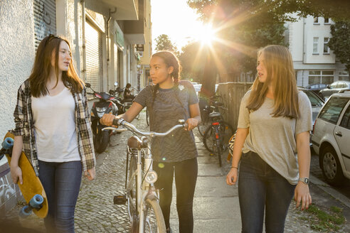 Three teenage girls on pavement with bicycle and skateboard - OJF000107