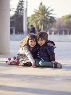 Spain, Girona, smiling  little boy and girl sitting side by side on the ground - XCF000057