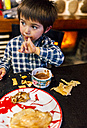 Portrait of little boy eating pancakes and drinking hot chocolate - MGOF001420