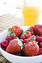 Strawberries and raspberries in a bowl and glass of orange juice - ABZF000200