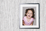 Framed photography of little girl hanging on striped wallpaper - ERLF000130