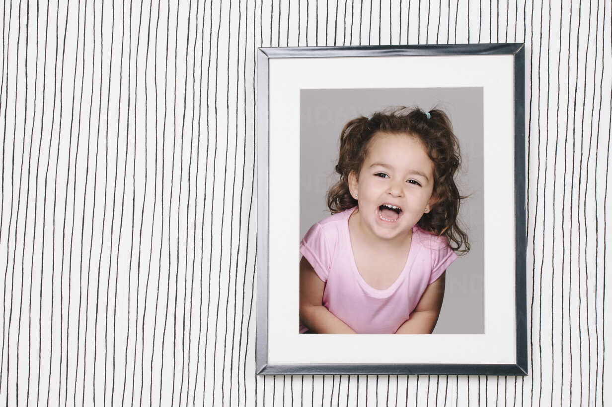 Framed photography of little girl hanging on striped wallpaper - ERLF000130 - Enrique Ramos/Westend61