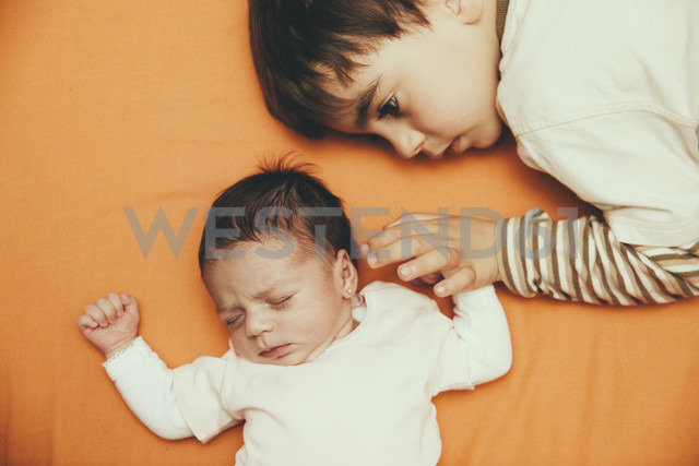 Newborn baby girl and brother lying on bed - ERLF000133 - Enrique Ramos/Westend61