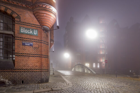 Germany, Hamburg, Fog in the Historic Warehouse district Speicherstadt at night - NKF000455