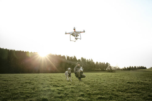 Man on a meadow flying drone while his dog watching - REAF000023