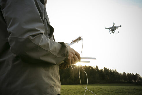 Man on a meadow flying drone - REAF000026