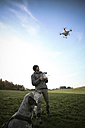 Man on a meadow flying drone while his dog watching - REAF000029