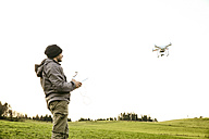 Man on a meadow flying drone - REAF000032