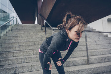 Tired woman resting in front of stairs after running - DAPF000018