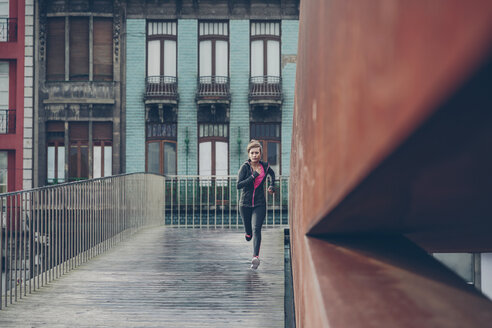 Mid adult woman running in the city - DAPF000024