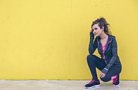 Woman wearing sports wear crouching in front of yellow wall - DAPF000030