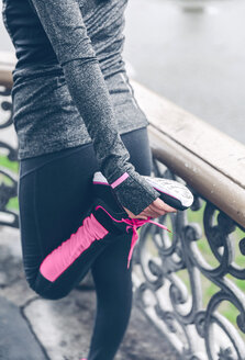 Mid adult woman warming up before running - DAPF000036