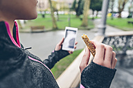Woman eating cereal bar after training and holding smart phone - DAPF000039