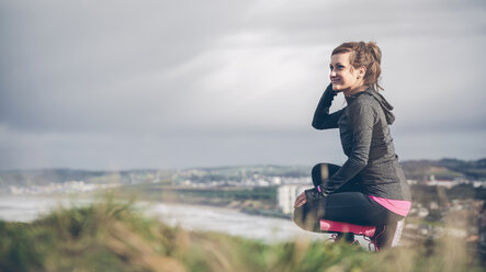 Sporty mid adult woman on cliff looking at sea - DAPF000042