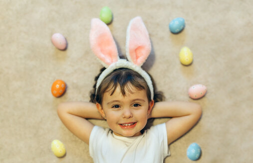 Portrait of happy little girl lying on the floor between Easter eggs - MGOF001423