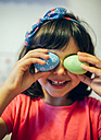 Little girl covering her eyes with  Easter eggs - MGOF001426