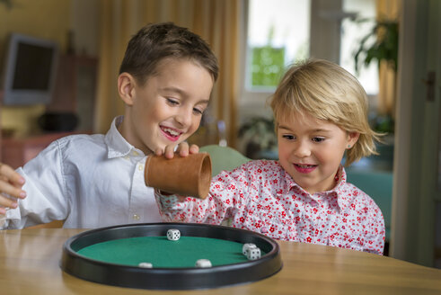 Brother and sister doing a game of dice together - EJWF000766