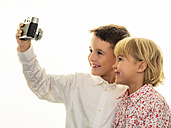 Smiling brother and sister taking a selfie with old-fashioned camera - EJWF000769