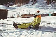 Italy, Val Venosta, Slingia, boy sleighing down a snowy hill - MFF002708