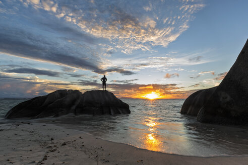 Seychelles, La Digue, beach, man standing on granite rock at sunset - FOF008427