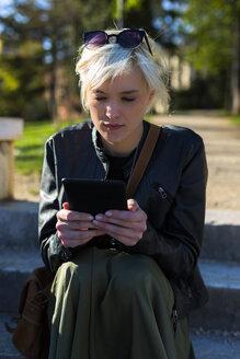 Portrait of blond woman reading an ebook - GIOF000735