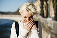 Italy, Verona, blond woman covering mouth with her hands - GIOF000747