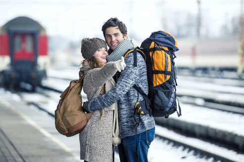 Smiling young couple embracing on station platform - HAPF000198