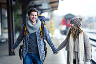 Happy young couple on station platform - HAPF000201