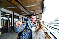 Happy young couple on station platform taking a selfie - HAPF000204