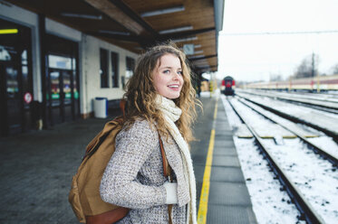 Smiling teenage girl on station platform - HAPF000207