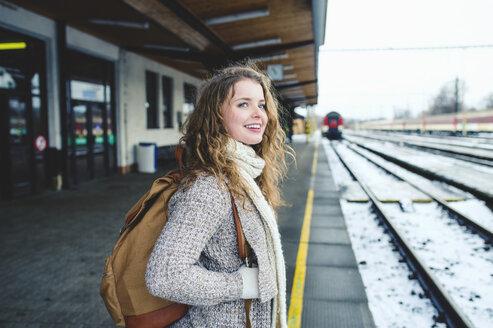 Smiling teenage girl on station platform - HAPF000207