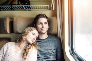 Smiling young couple in train car looking out of window - HAPF000213