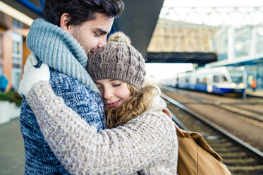 Smiling young couple embracing on station platform - HAPF000216