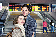 Smiling young couple embracing in station concourse - HAPF000219