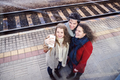 Three friends on station platform taking a selfie - HAPF000222