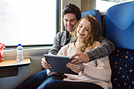 Smiling young couple in train car using digital tablet - HAPF000225