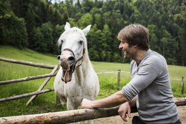 Germany, Bavaria, Bad Toelz, man with horse at fence - TKF000428