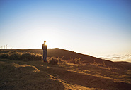 Portugal, Madeira, man looking at sunset in rural landscape - REAF000048