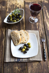 Plate with baguette slices and olives and a glass of red wine - SARF002542