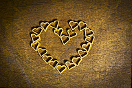 Heart-shaped noodles forming a heart on wood - MAEF011277