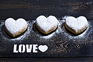 The word 'Love' stenciled with icing sugar and three heart-shaped crullers on dark wood - MAEF011280