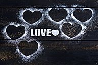 Hearts and the word 'Love' stenciled with icing sugar on dark wood - MAEF011283