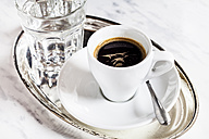 Cup of espresso and glass of water on metal tray - SBDF002689