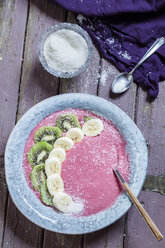 Bowl of vegan raspberry smoothie garnished with kiwi and banana slices - SBDF002695