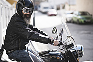 Spain, Jaen, portrait of bearded biker wearing helmet and goggles sitting on his sidecar motorcycle - JASF000394